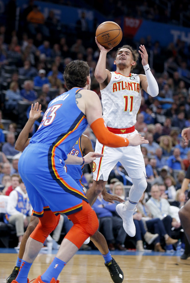 Photo - Atlanta's Trae Young (11) shoots in front of Oklahoma City's Mike Muscala (33) during the NBA basketball game between the Oklahoma City Thunder and the Atlanta Hawks at the Chesapeake Energy Arena in Oklahoma City,Friday, Jan. 24, 2020.  [Sarah Phipps/The Oklahoman]