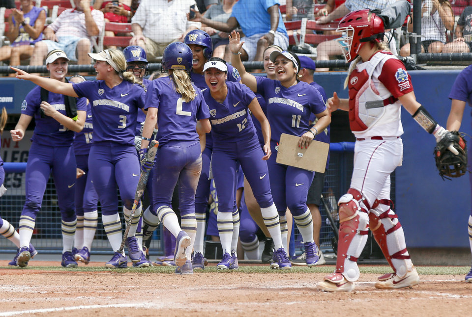 Photo - Washington celebrates near Oklahoma's Lea Wodach (15) after Trysten Melhart (2) scored in the top of the fifth inning during the second game of the Women's College World Series between the Oklahoma Sooners (OU) and Washington Huskies at USA Softball Hall of Fame Stadium in Oklahoma City, Thursday, May 31, 2018. Washington won 2-0. Photo by Nate Billings, The Oklahoman