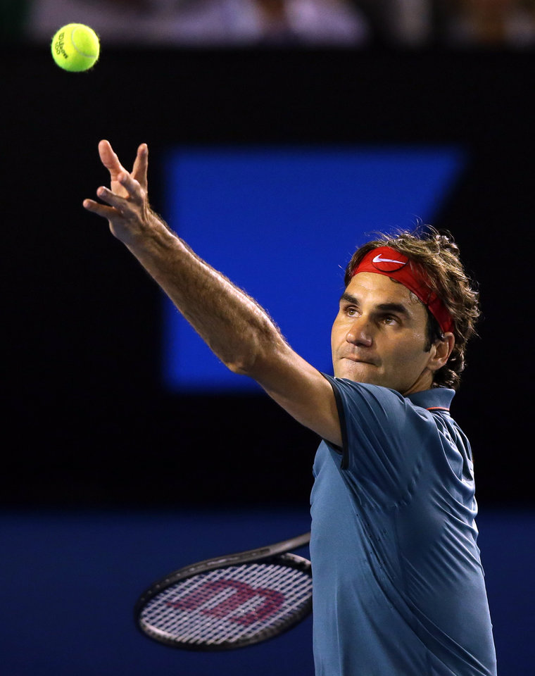 Photo - Roger Federer of Switzerland  serves to Jo-Wilfried Tsonga of France during their fourth round match at the Australian Open tennis championship in Melbourne, Australia, Monday, Jan. 20, 2014.(AP Photo/Aaron Favila)