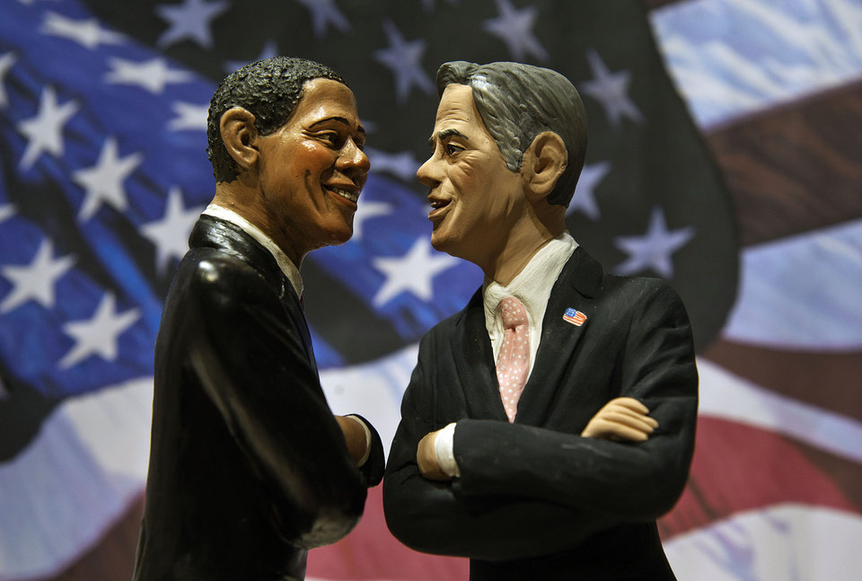 Photo -   Two statuettes depicting President Barack Obama, left, and Republican rival Mitt Romney are backdropped by the Stars and Stripes in a shop which sells Christmas nativity figures in Naples, Italy, Monday, Oct. 22, 2012, hours ahead of their third and final presidential debate in Boca Raton, Florida. (AP Photo/Salvatore Laporta)