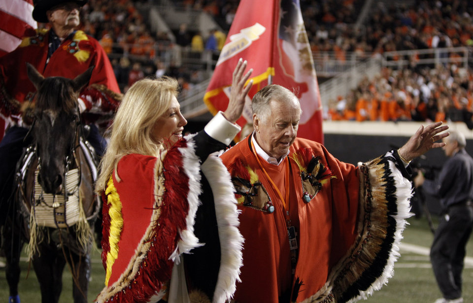 Photo - Madeleine and Boone Pickens lead horses from the Wild Horse Foundation onto the field during halftime of the  college football game between Oklahoma State University (OSU) and the University of Colorado (CU) at Boone Pickens Stadium in Stillwater, Okla., Thursday, Nov. 19, 2009. Photo by Sarah Phipps, The Oklahoman