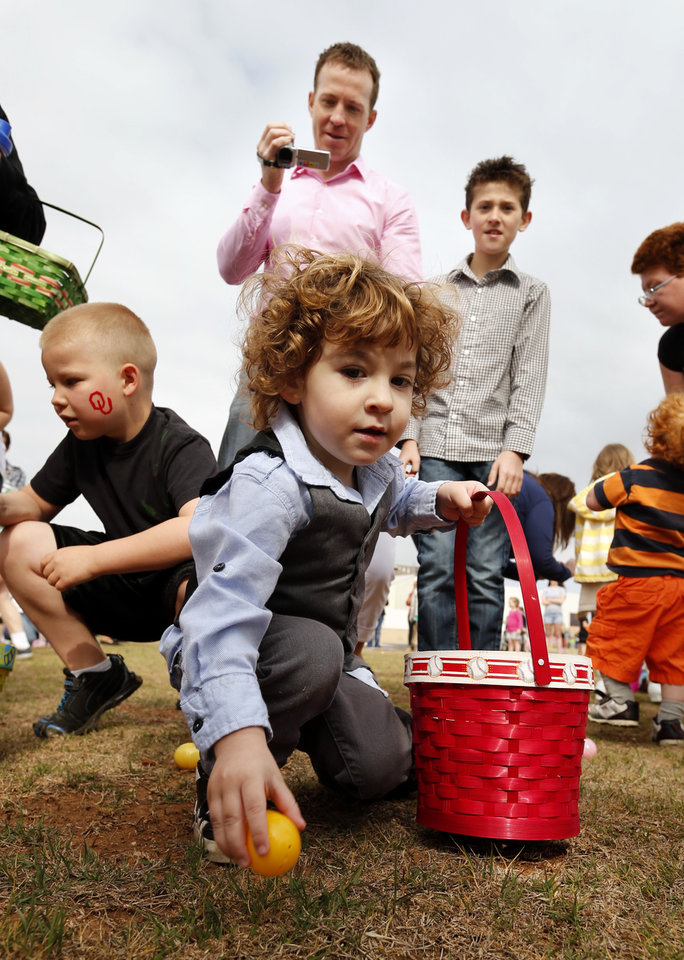 Acen Wilson, 2, reaches for a prize as his father John and big brother Aden, 11, follow at the Cleveland County YMCA Community Easter Egg Hunt on Saturday, March 30, 2013 in Norman, Okla.  Photo by Steve Sisney, The Oklahoman