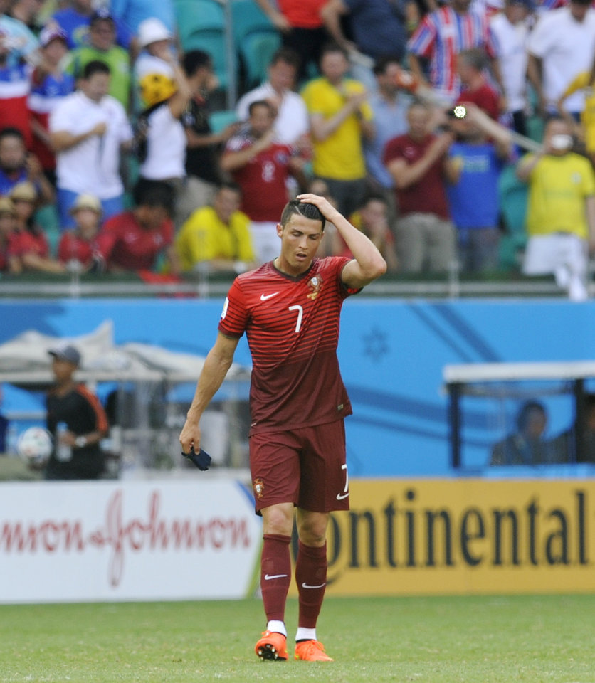 Photo - Portugal's Cristiano Ronaldo walks off the pitch following Portugal's 4-0 loss to Germany during the group G World Cup soccer match between Germany and Portugal at the Arena Fonte Nova in Salvador, Brazil, Monday, June 16, 2014.  (AP Photo/Paulo Duarte)