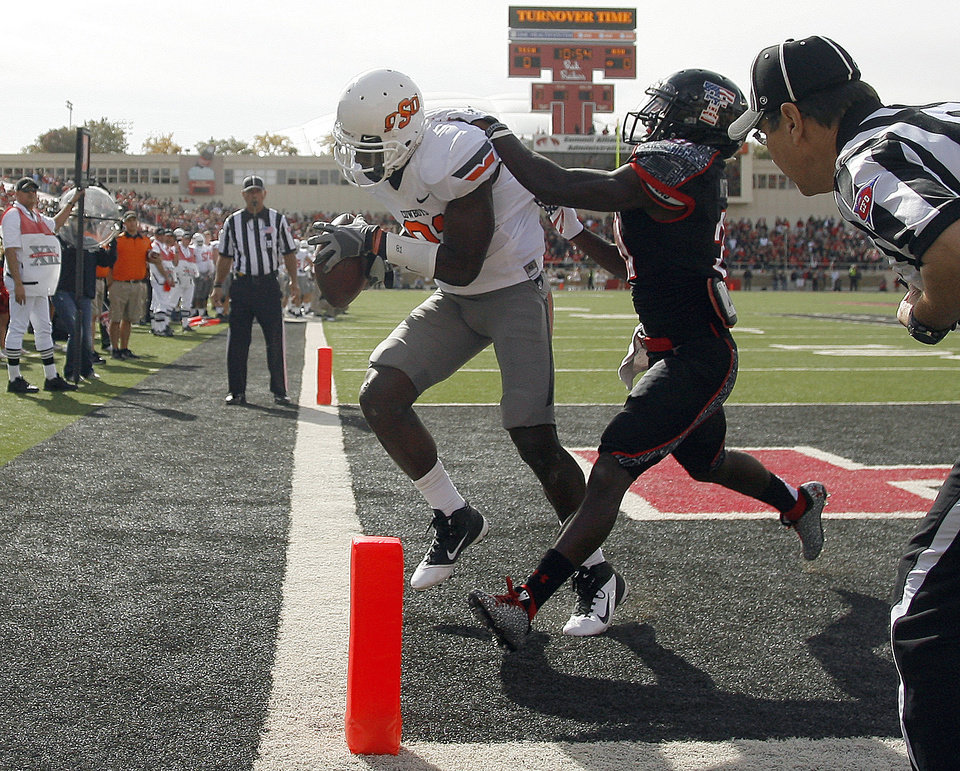 Photo - Oklahoma State Cowboys's Justin Blackmon (81) scores a touchdown as Eugene Neboh (31) tries to bring him down during a college football game between Texas Tech University (TTU) and Oklahoma State University (OSU) at Jones AT&T Stadium in Lubbock, Texas, Saturday, Nov. 12, 2011.  Photo by Sarah Phipps, The Oklahoman  ORG XMIT: KOD