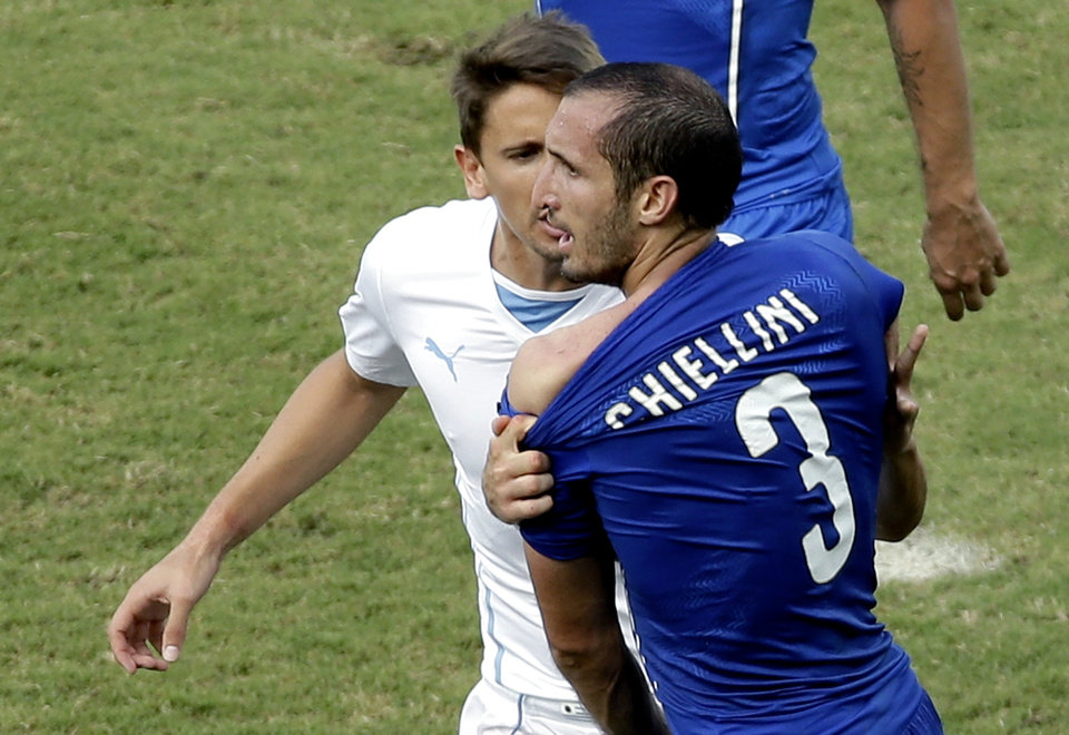 Photo - Italy's Giorgio Chiellini complains after Uruguay's Luis Suarez ran into his shoulder with his teeth during the group D World Cup soccer match between Italy and Uruguay at the Arena das Dunas in Natal, Brazil, Tuesday, June 24, 2014. (AP Photo/Hassan Ammar)