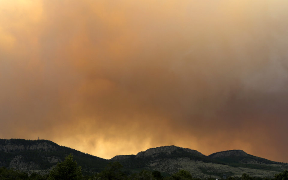 Photo - Wildfire smoke blankets a ridge Sunday, June 23, 2013, near Alpine, Colo. A large wildfire near a popular summer retreat in southern Colorado continues to be driven by winds and fueled by dead trees in a drought-stricken area, authorities said Sunday. (AP Photo/Gregory Bull)