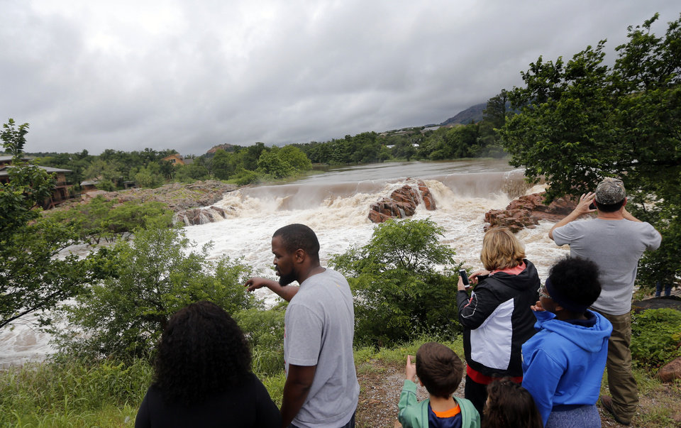 Photo - People watch the rushing water at an overflowing Medicine Creek in Medicine Park, Okla., Sunday, May 24, 2015. Photo by Sarah Phipps, The Oklahoman