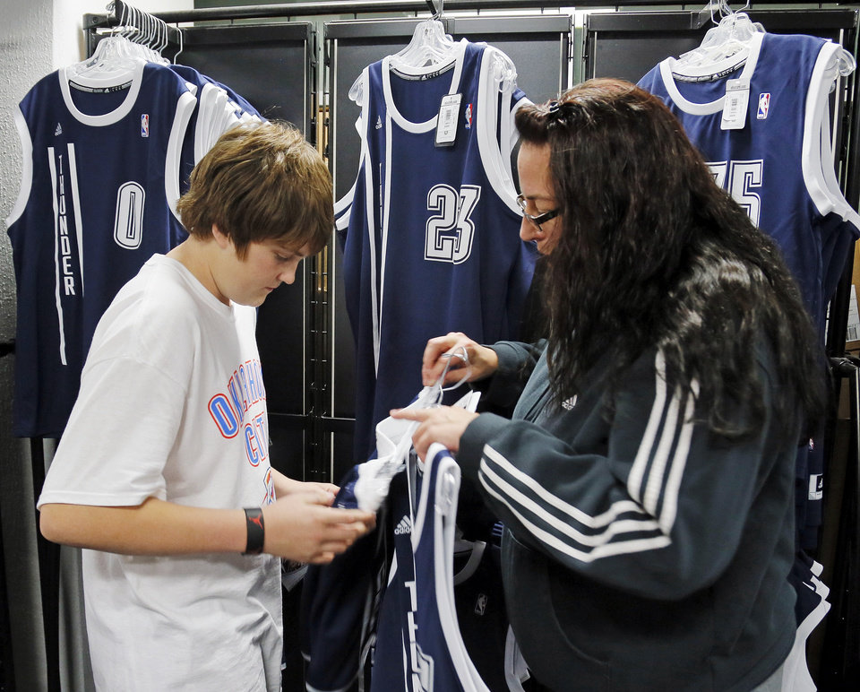 Photo - Jaxon Sykes, 14, and his stepmother, Melanie Armos, check the sizes on the new alternate Thunder uniforms before an NBA basketball game between the Detroit Pistons and the Oklahoma City Thunder at the Chesapeake Energy Arena in Oklahoma City, Friday, Nov. 9, 2012. Photo by Nate Billings, The Oklahoman