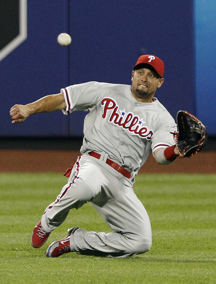 FILE- In this July 5, 2012, file photo, Philadelphia Phillies center fielder Shane Victorino catches a ball hit by New York Mets' Jordany Valdespin for an out during the seventh inning of a baseball game in New York. . A person familiar with the situation says the Phillies have traded the two-time All-Star center fielder to the Los Angeles Dodgers for two pitchers on Tuesday, July 31, 2012. (AP Photo/Frank Franklin II, File)