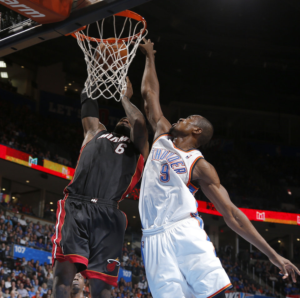 Photo - Miami's LeBron James (6) dunks the ball beside Oklahoma City's Serge Ibaka (9) before falling to the ground with a bloody nose during an NBA basketball game between the Oklahoma City Thunder and the Miami Heat at Chesapeake Energy Arena in Oklahoma City, Thursday, Feb. 20, 2014. Oklahoma CIty lost 103-81. Photo by Bryan Terry, The Oklahoman