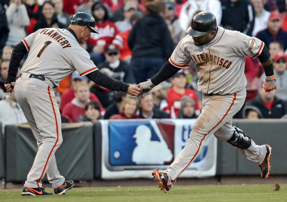 Photo -   San Francisco Giants' Pablo Sandoval is congratulated by third base coach Tim Flannery (1) after hitting a two-run home run against the Cincinnati Reds in the seventh inning of Game 4 of the National League division baseball series, Wednesday, Oct. 10, 2012, in Cincinnati. (AP Photo/Michael Keating)