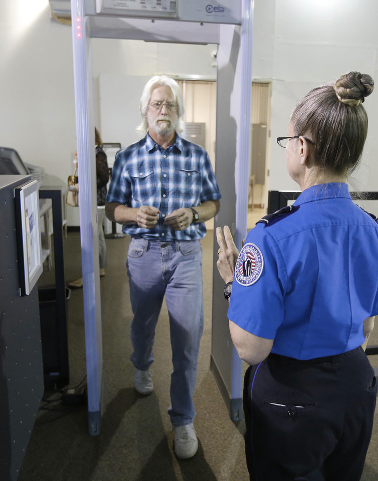 Photo - Transportation Security Administration Office Doris Butler monitors the metal detector as Joe Varee, of Erie, Pa., passes through security at Will Rogers World Airport. TSA Pre-Check is now available at 100 airports nationwide, including in Oklahoma City and Tulsa.  Steve Gooch - The Oklahoman