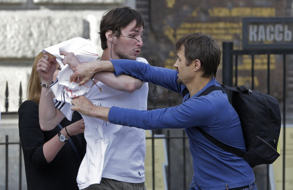 Photo -   An Orthodox believer, right, pulls at a poster held by a demonstrator, whose spectacles have been knocked from his head, standing in a picket in support of the Russian punk group Pussy Riot whose members face prison for a stunt against President Vladimir Putin, in front of the Savior of Spilled Blood Cathedral in St.Petersburg, Russia, Friday, Aug. 17, 2012. A Moscow judge has sentenced each of three members of the provocative punk band Pussy Riot to two years in prison on hooliganism charges following a trial that has drawn international outrage as an emblem of Russia's intolerance to dissent. ( AP Photo/Dmitry Lovetsky)