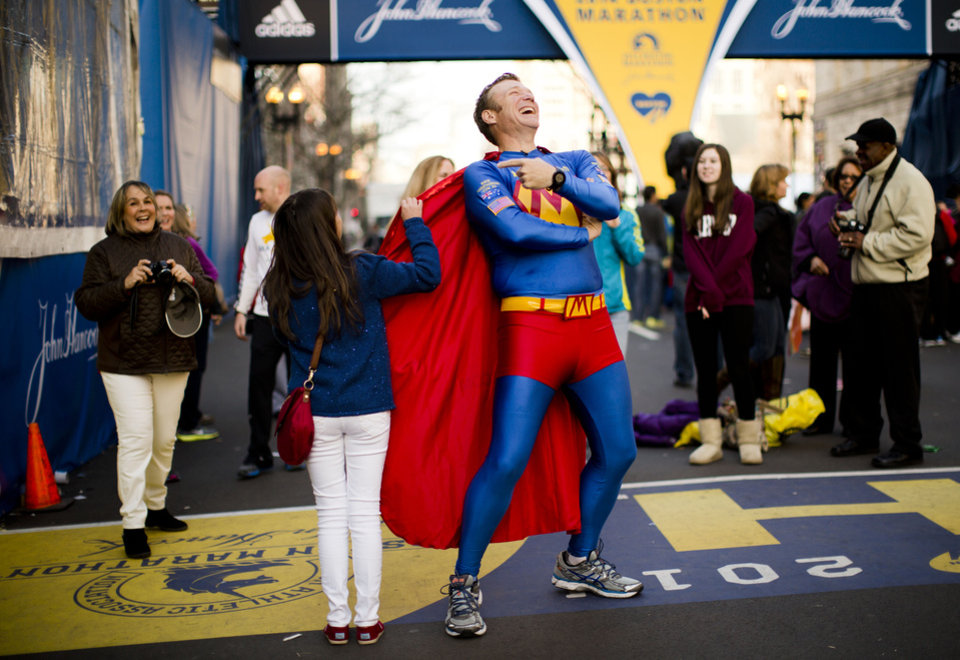 "Photo - Trent Morrow of Sydney, Australia, also know as ""Marathon Man"" laughs as Andrea Olivo of Venezuela tugs on his cape as she has her photo made ahead of Monday's 118th Boston Marathon, Sunday, April 20, 2014, in Boston. Morrow says Monday's marathon will be his 200th run since Jan. 1, 2013. (AP Photo/Matt Rourke)"