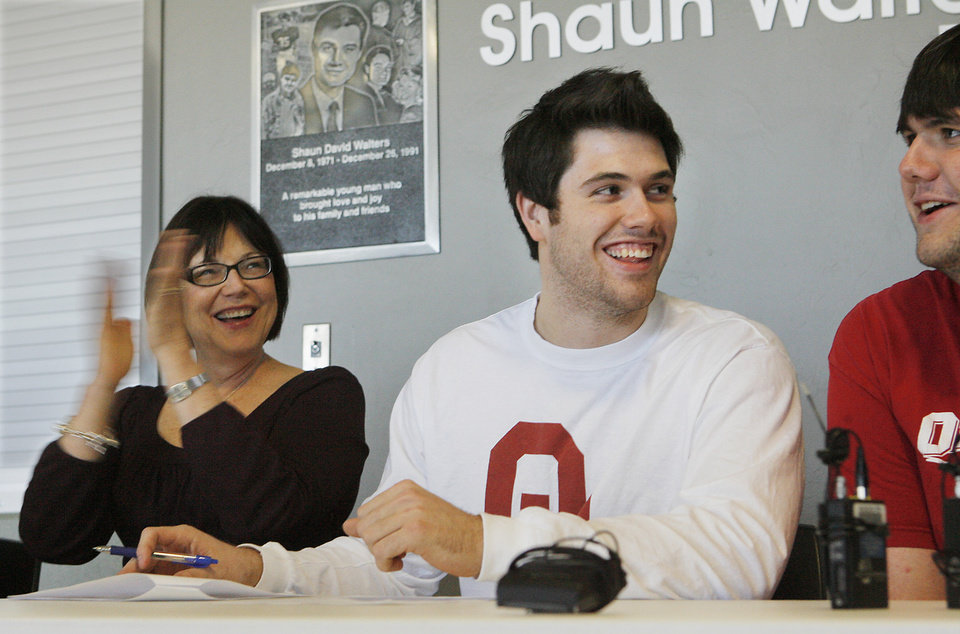 Photo - Gabe Ikard, Bishop McGuinness, center, jokes with his brother Sam a junior at OU,  as his mom, Becky claps after signing a letter of intent with OU, Wednesday, February 4, 2009.  Photo by David McDaniel/The Oklahoman