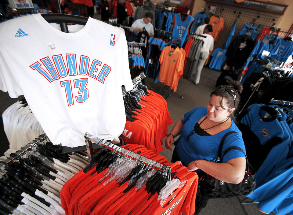 Photo - Alicia Henry looks through Oklahoma City Thunder merchandise at the USA Screen Printing and Embroidery's House of Bedlam shop, 3100 S. Meridian, in Oklahoma City, Wednesday, June 13, 2012. Photo by Nate Billings, The Oklahoman