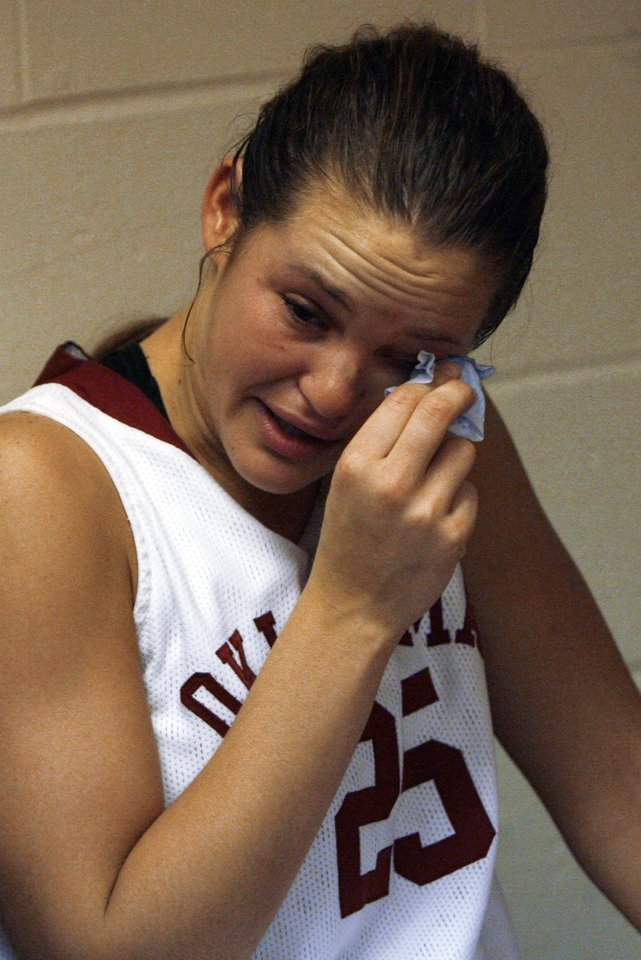 Photo - Sooner Whitney Hand wipes tears in the locker room after the University of Oklahoma is defeated by Louisville 61-59 at the 2009 NCAA women's basketball tournament Final Four in the Scottrade Center in Saint Louis, Missouri on Sunday, April 5, 2009. Photo by Steve Sisney, The Oklahoman