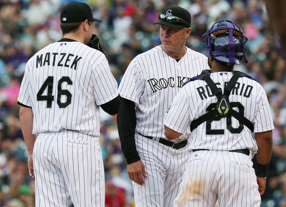 Photo - Colorado Rockies starting pitcher Tyler Matzek, left, confers with pitching coach Jim Wright, center, and catcher Wilin Rosario after Matzek walked Milwaukee Brewers' Ryan Braun in the fifth inning of a baseball game in Denver on Sunday, June 22, 2014. Matzek gave up a single to the Brewers' next batter, Jonathan Lucroy, that drove in two runners. (AP Photo/David Zalubowski)