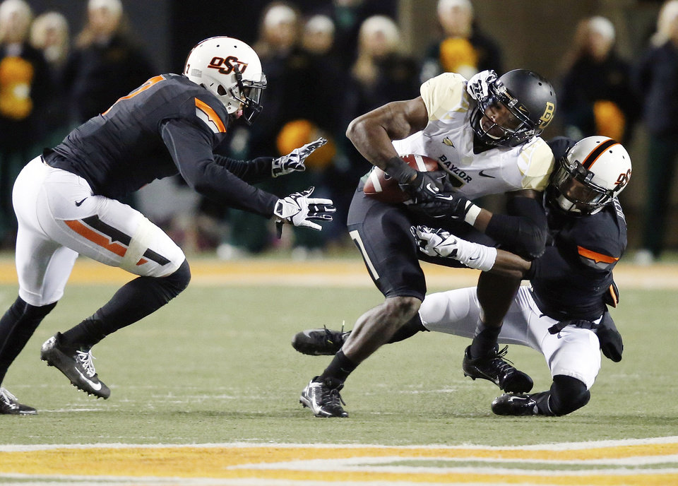 Photo - Baylor wide receiver Antwan Goodley (5) is tackled by Oklahoma State cornerback Kevin Peterson, right, in the second quarter of an NCAA college football game in Stillwater, Okla., Saturday, Nov. 23, 2013. (AP Photo/Sue Ogrocki)