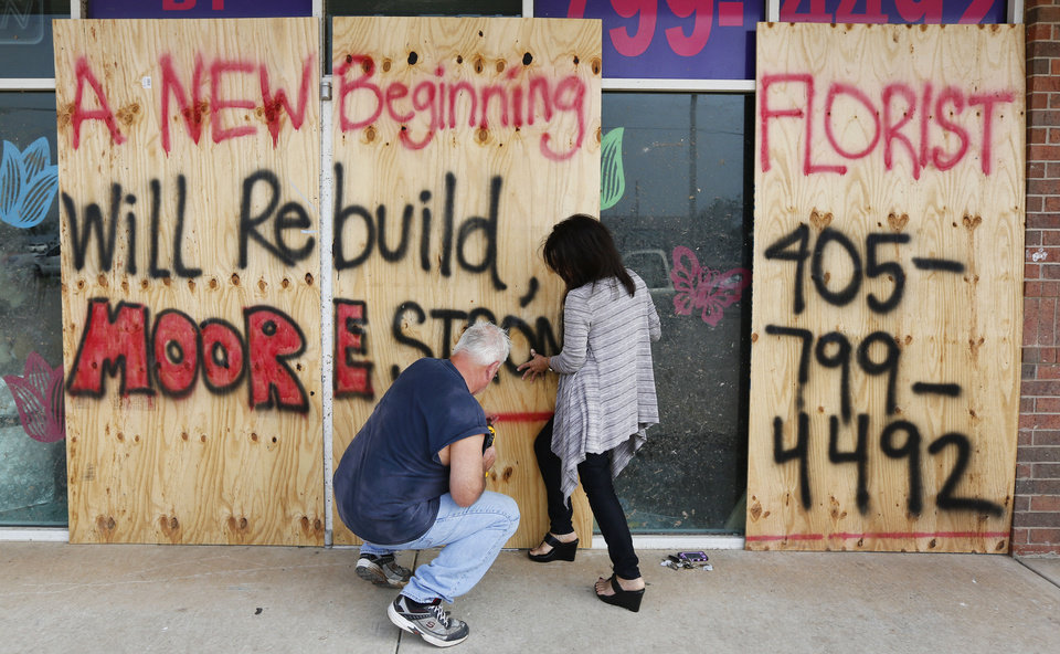 Photo - Doug Juergens and Lu Zapp put boards up on A New Beginning Florist in Moore. The flower shop, at SW 4 and Telephone Road, was damaged by a massive tornado that tore through Moore on Monday.  Steve Gooch - The Oklahoman