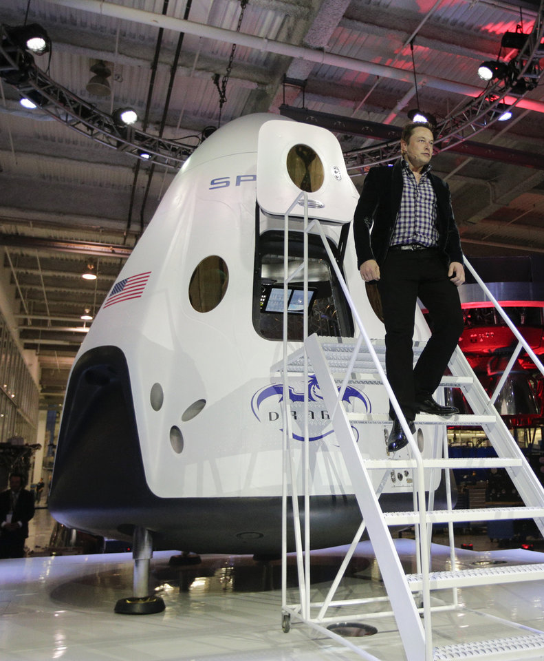 Photo -  Elon Musk, of SpaceX, walks down the steps Thursday while introducing the SpaceX Dragon V2 spacecraft in Hawthorne, Calif. AP Photo   Jae C. Hong -  AP