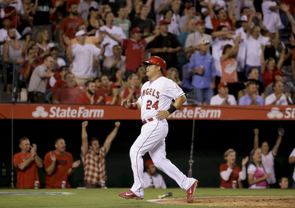 Photo - Los Angeles Angels' Hank Conger scores on double by Mike Trout during the fourth inning of a baseball game against the Los Angeles Angels in Anaheim, Calif., Tuesday, Aug. 26, 2014. (AP Photo/Chris Carlson)