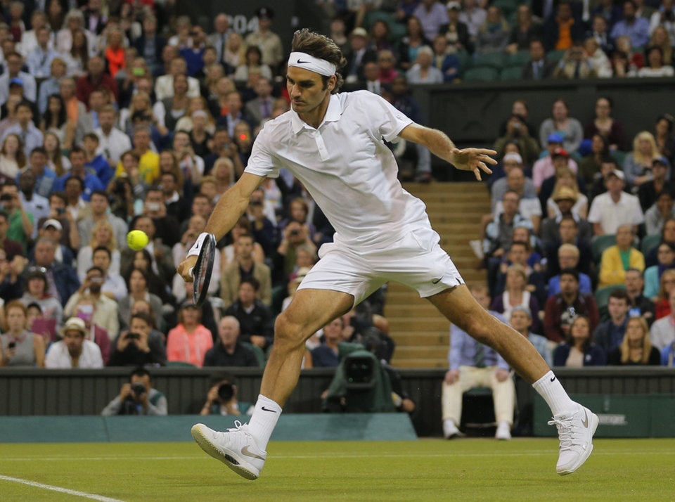 Photo - Roger Federer of Switzerland plays a return to Gilles Muller of Luxembourg plays a return to during their match at the All England Lawn Tennis Championships in Wimbledon, London, Thursday, June 26, 2014. (AP Photo/Pavel Golovkin)