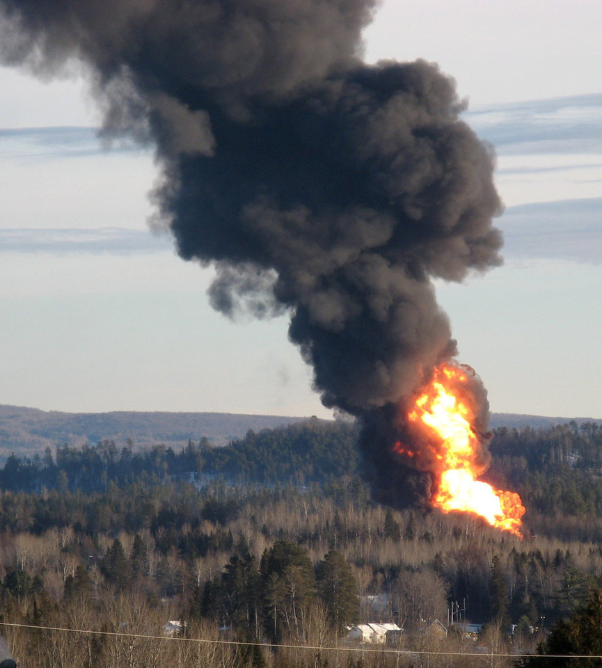 Photo - A large fireball rises from the site of a train derailment in New Brunswick, Canada, Friday, Jan. 10, 2014 as officials used a controlled explosion to blast holes in three tanker cars in the hopes of fighting a large fire that continues to burn two and half days after the incident. Canadian National Railway spokesman Jim Feeny says the procedure they used is known as vent and burn, and preliminary indications are that it went according to plan. (AP Photo/The Canadian Press, Kevin Bissett)