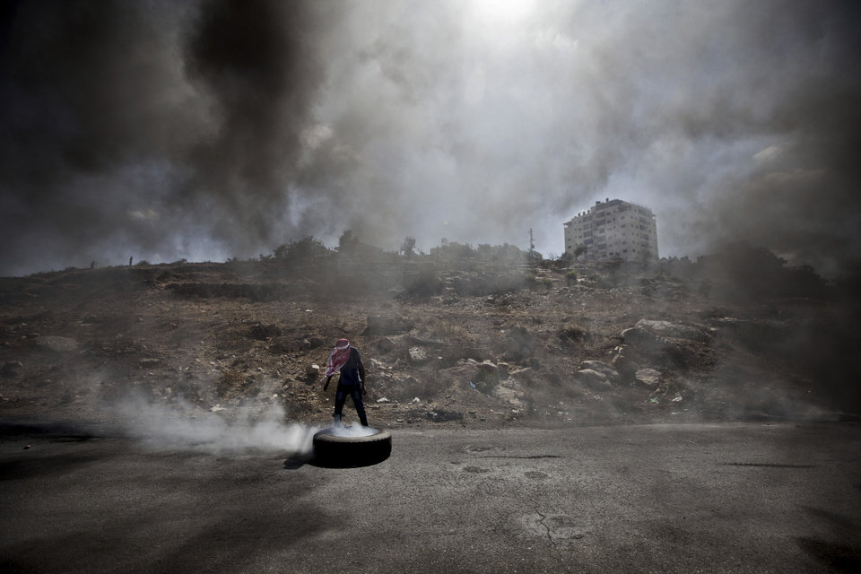 Photo - A Palestinian man burns a tire during clashes with Israeli soldiers following a protest against the Israeli offensive in Gaza, outside Ofer, an Israeli military prison near the West Bank city of Ramallah, Friday, July 18, 2014. Israeli troops pushed deeper into Gaza on Friday to destroy rocket launching sites and tunnels, firing volleys of tank shells and clashing with Palestinian fighters in a high-stakes ground offensive meant to weaken the enclave's Hamas rulers. (AP Photo/Majdi Mohammed)