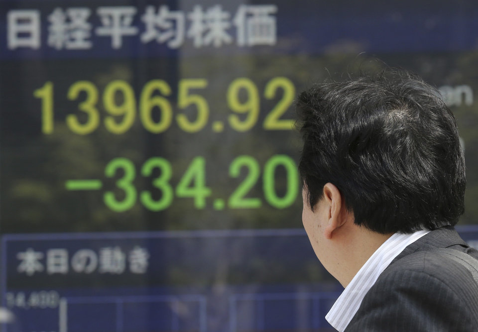 Photo - A man looks at an electronic stock board of a securities firm in Tokyo, Friday, April 11, 2014. Tokyo's Nikkei 225 stock average fell more than 400 points at one point in morning trading. (AP Photo/Koji Sasahara)