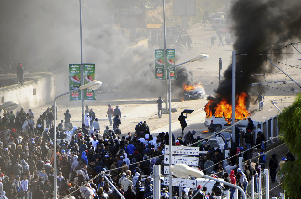 Photo - Cars burn next to the cemetery where thousands of Tunisians are gathered at el Jallez cemetery to attend the funerals of slain opposition leader Chokri Belaid, near Tunis, Friday Feb. 8, 2013. The Wednesday Feb. 6 assassination of prominent government critic Chokri Belaid plunged the country into one of its deepest political crises since the overthrow of the dictatorship in 2011.(AP Photo/Hassene Dridi)