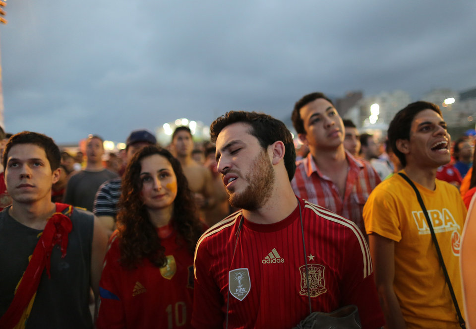 Photo - A frustrated soccer fan looks away from a live broadcast of the group B World Cup match between Chile and Spain inside the FIFA Fan Fest area on Copacabana beach, in Rio de Janeiro, Brazil, Wednesday, June 18, 2014. Chile defeated Spain, the defending champs 2-0. (AP Photo/Leo Correa)