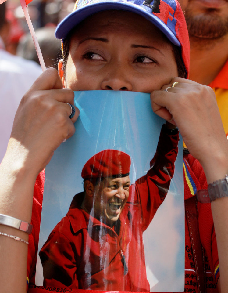 Photo - A woman holds a picture of Venezuela's President Hugo Chavez during an event commemorating the violent street protests of 1989 known as the