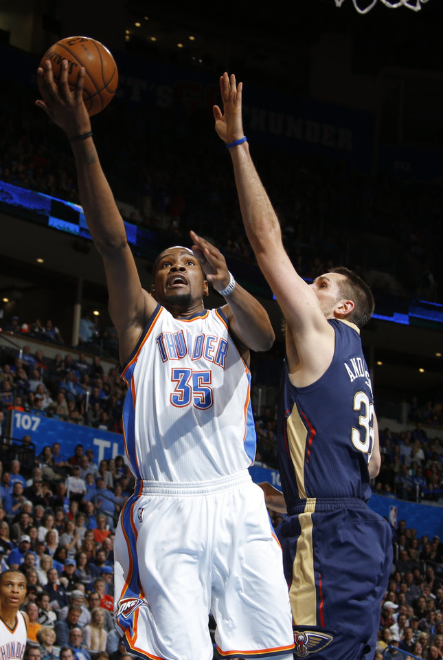 Photo - Oklahoma City's Kevin Durant (35) goes to the basket past New Orleans' Ryan Anderson (33) during an NBA game between the Oklahoma City Thunder and the New Orleans Pelicans at Chesapeake Energy Arena on Friday, Feb. 6, 2015. Photo by Bryan Terry, The Oklahoman