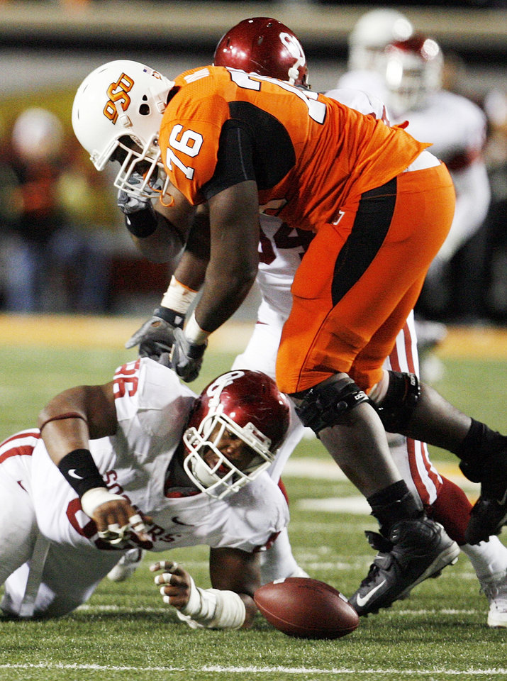 Photo - OU's Adrian Taylor (86), underneath Russell Okung (76) of OSU, recovers a fumble by Zac Robinson (not pictured) in the fourth quarter of the college football game between the University of Oklahoma Sooners (OU) and Oklahoma State University Cowboys (OSU) at Boone Pickens Stadium on Saturday, Nov. 29, 2008, in Stillwater, Okla. STAFF PHOTO BY NATE BILLINGS