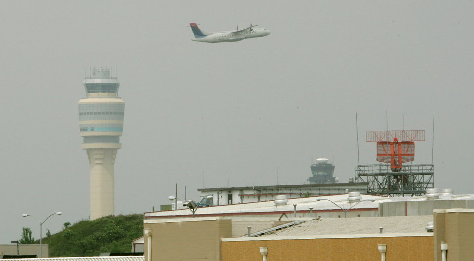 Photo - A Delta airplane takes off between the new control tower, left, and the airport's radar station, right, at Hartsfield-Jackson International Airport in Atlanta, May, 8, 2006. (AP Photo/John Amis)