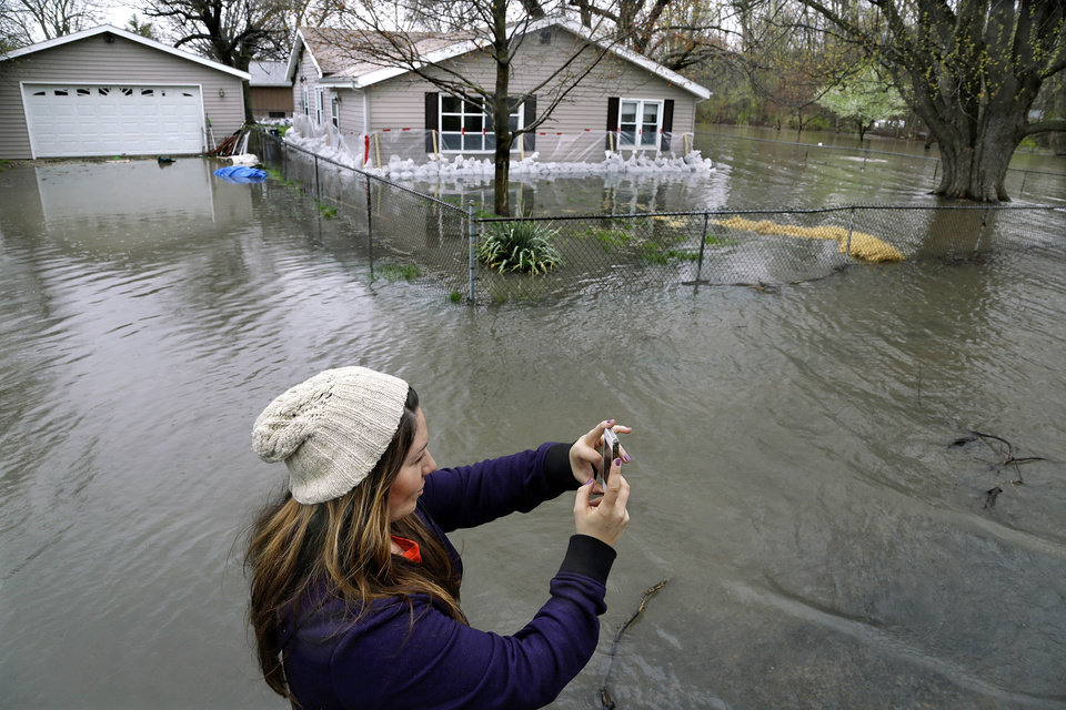 Jennifer Rock uses her cell phone to take photos to send to a friend of flooding from the Illinois River Tuesday, April 23, 2013, in Spring Bay Ill. Floodwaters are rising to record levels along the Illinois River in central Illinois.  (AP Photo/Seth Perlman)
