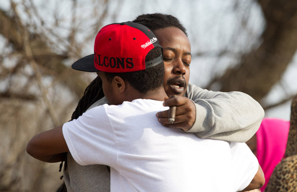 Photo - Leaman Joe, left, hugs Michael Parker, at the crash site that killed their friends on Park Ave. in Warren, Ohio on Sunday, March 10, 2013. (AP Photo/Scott R. Galvin)