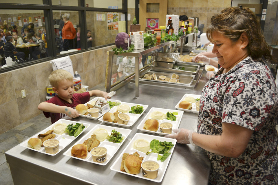 Kindergartener Jayden Drake and cafeteria manager Kay Rainwater during lunch at Centennial Elementary School in Mustang that is part of a partnership with Made in Oklahoma, March 8, 2012. Photo by Zeke Campfield, The Oklahoman