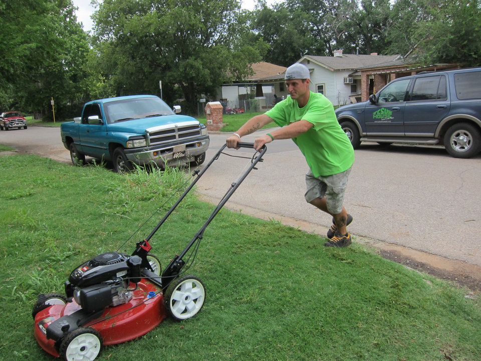Photo -  Jesus House resident Josh Bibb, 26, mows the lawn of an Orchard Park resident as part of the Jesus House's Adopt-A-Block program. Photo by Carla Hinton, The Oklahoman