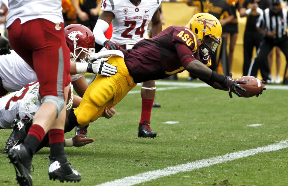 Photo -   Arizona State's Marion Grice, right, dives in for a touchdown as he eludes several Washington State defenders during the first half in an NCAA college football game Saturday, Nov. 17, 2012, in Tempe, Ariz. Arizona State defeated the Washington State 46-7.(AP Photo/Ross D. Franklin)