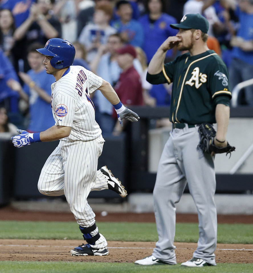 Photo - New York Mets' Travis d'Arnaud (15) trots past Oakland Athletics first baseman Brandon Moss (37) after hitting a third-inning three-run home run off Oakland Athletics starting pitcher Scott Kazmir in an interleague baseball game in New York, Tuesday, June 24, 2014. The Mets won 10-1. (AP Photo/Kathy Willens)