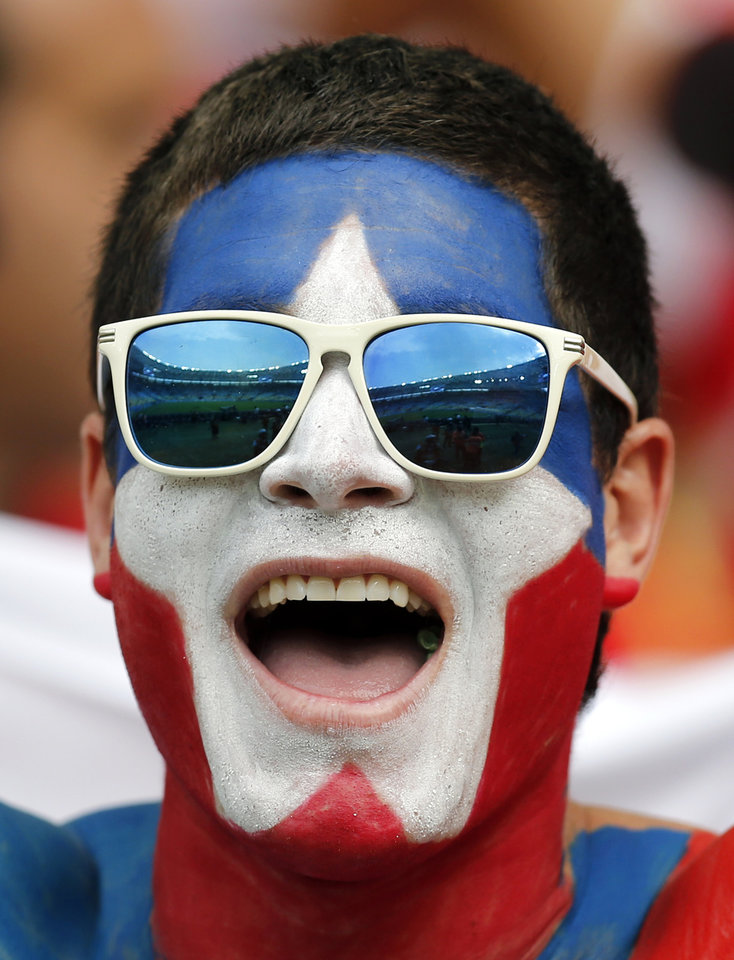 Photo - A Chilean fan cheers before the group B World Cup soccer match between Spain and Chile at the Maracana Stadium in Rio de Janeiro, Brazil, Wednesday, June 18, 2014.  (AP Photo/Frank Augstein)