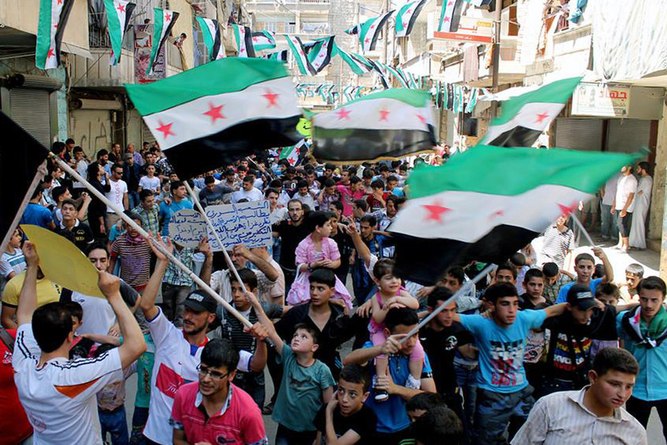 This citizen journalism image provided by Aleppo Media Center AMC which has been authenticated based on its contents and other AP reporting, shows anti-Syrian regime protesters holding Syrian revolution flags, during a demonstration in the neighborhood of Bustan Al-Qasr in Aleppo, Syria, Friday, June 28, 2013. Intense shelling by Syrian government troops on a village in the country\'s south killed several women and girls overnight as forces loyal to President Bashar Assad pushed ahead with an offensive against rebels near the border with Jordan, activists said Friday. (AP Photo/Aleppo Media Center AMC)