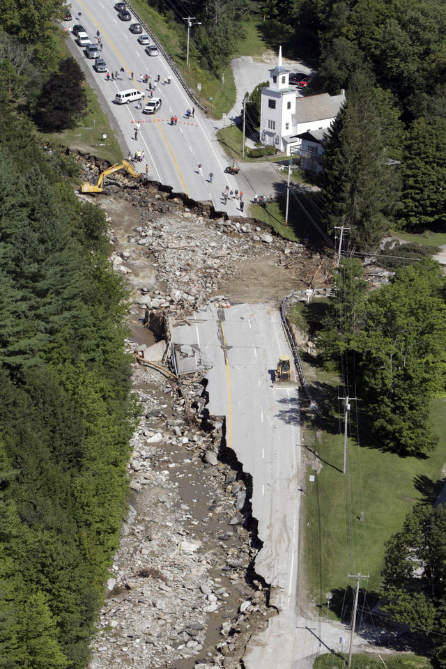 Photo - FILE -- This Aug. 30, 2011 file aerial photograph shows destruction of Route 4 in Killington, Vt., after Tropical Storm Irene passed through New England. Global warming is rapidly turning America into a stormy and dangerous place, with rising seas and disasters upending lives from flood-stricken Florida to the wildfire-ravaged West, according to a new U.S. federal scientific report released Tuesday, May 6, 2014.   (AP Photo/Toby Talbot, File)