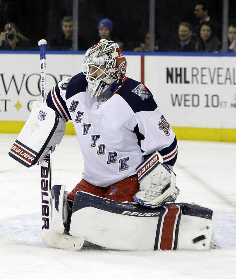Photo - New York Rangers goalie Henrik Lundqvist (30), of Sweden, stops a shot on-goal during the first period of an NHL hockey game against the New York Islanders, Friday, Jan. 31, 2014, in New York. (AP Photo/Frank Franklin II)