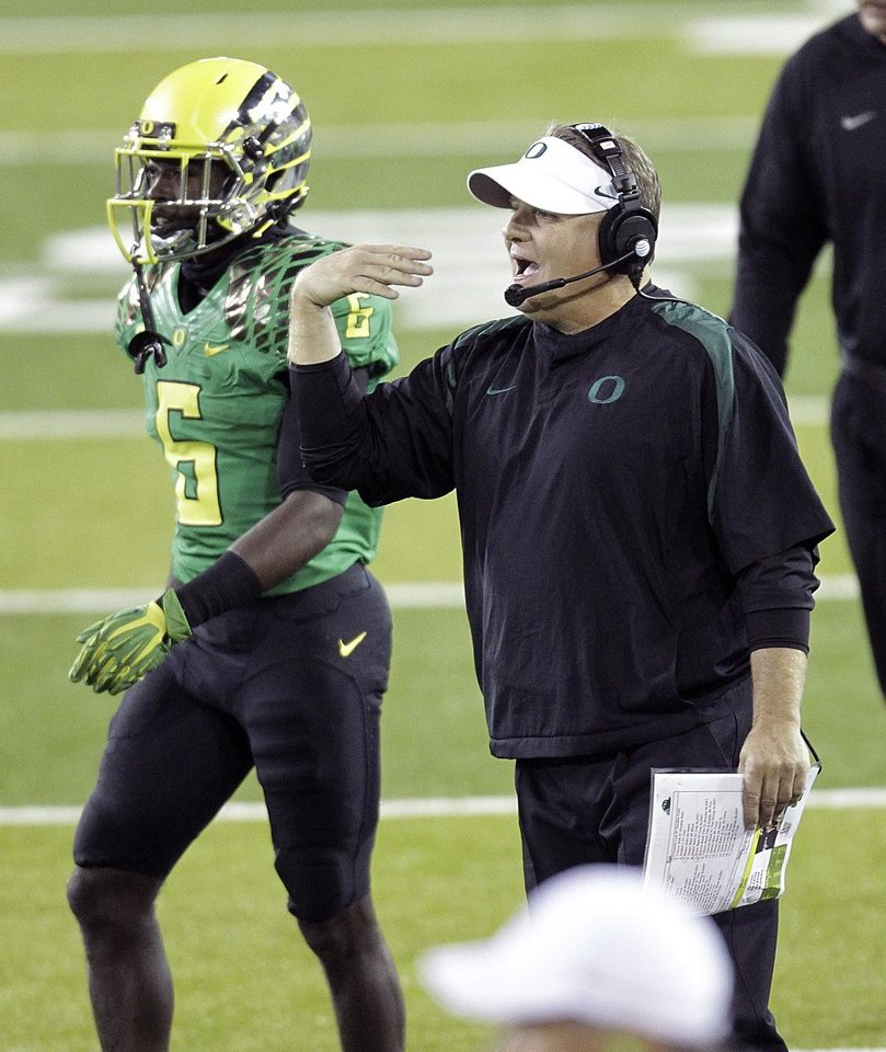 Oregon football coach Chip Kelly, right, gives direction from the sideline as running back De\'Anthony Thomas stands at left during the second half of their NCAA college football game against Washington in Eugene, Ore., Saturday, Oct. 6, 2012. Oregon beat Washington 52-21.(AP Photo/Don Ryan)
