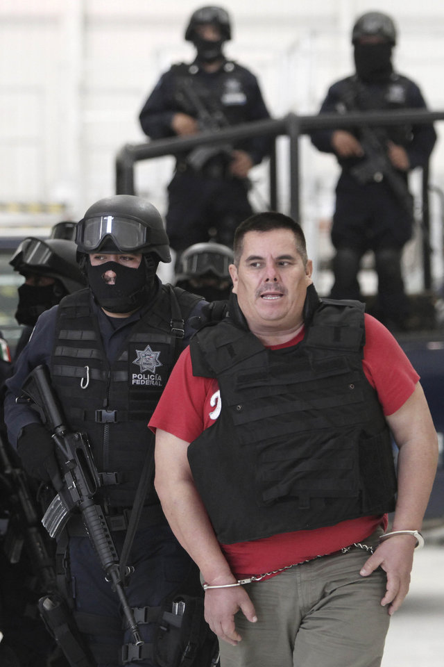 "A federal police officer escorts Jose de Jesus Mendez Vargas, aka, ""El Chango"" or ""The Monkey,"" alleged leader of Mexican La Familia drug cartel, during his presentation to the press in Mexico City, Wednesday, June 22, 2011. Mendez was arrested at a federal police checkpoint in the Mexican central state of Aguascalientes Tuesday, without confrontation or casualties according to authorities. The government had offered a $2.5 million reward for his capture. (AP Photo/Miguel Tovar)"