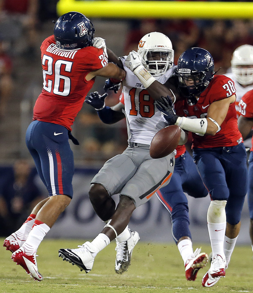 Photo - Arizona's Jourdon Grandon (26) and Jared Tevis (38) break up a pass intended for Oklahoma State's Blake Jackson (18) during the college football game between the University  of Arizona and Oklahoma State University at Arizona Stadium in Tucson, Ariz.,  Saturday, Sept. 8, 2012. Photo by Sarah Phipps, The Oklahoman