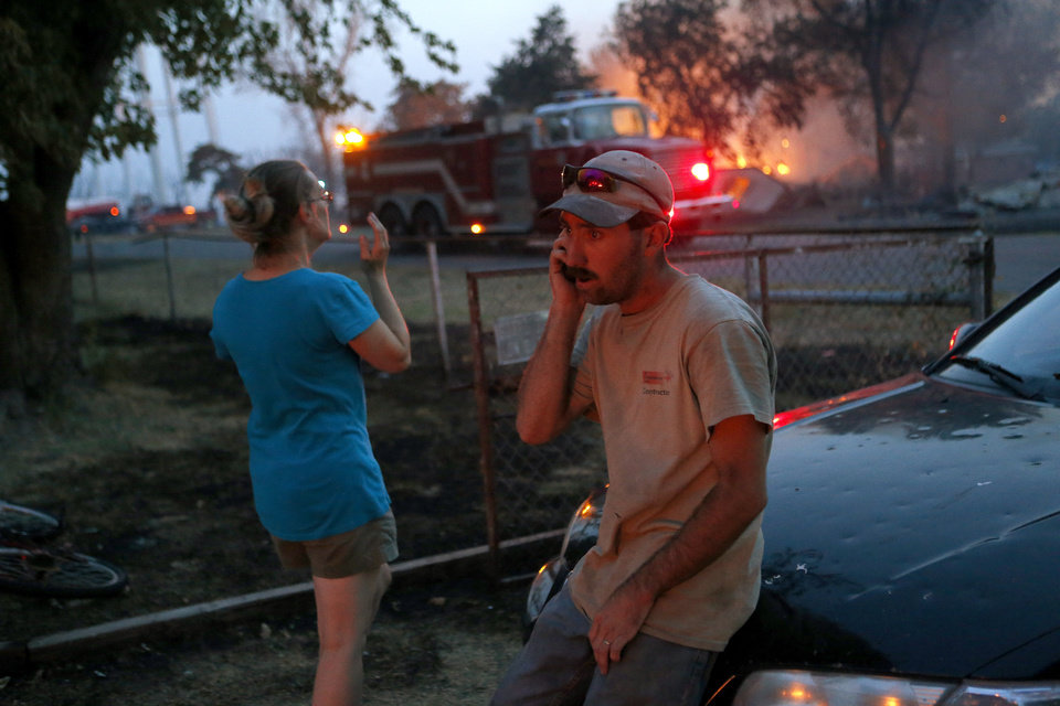 Tommy Turner talks on the phone as a fire burns in Luther, Okla., after wildfire moved through the area on Friday, August 3, 2012. Photo by Bryan Terry, The Oklahoman